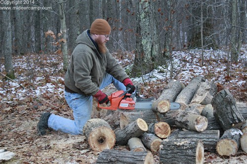 Kruger using a chainsaw to cut firewood